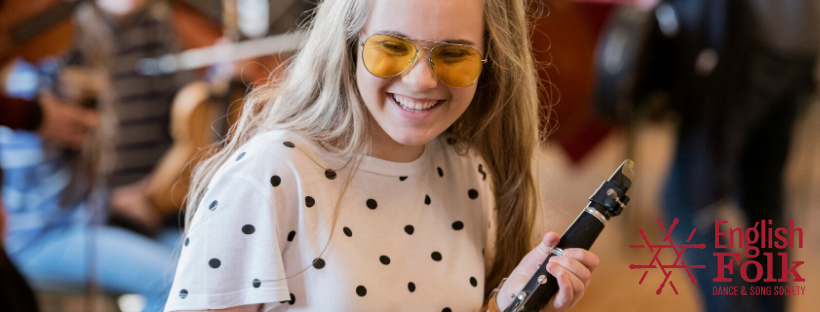 A blond girl is smiling. She is holding a clarinet, and wears yellow sunglasses and a white top with black polka dots.Behind her are the blurry figures of other musicians.