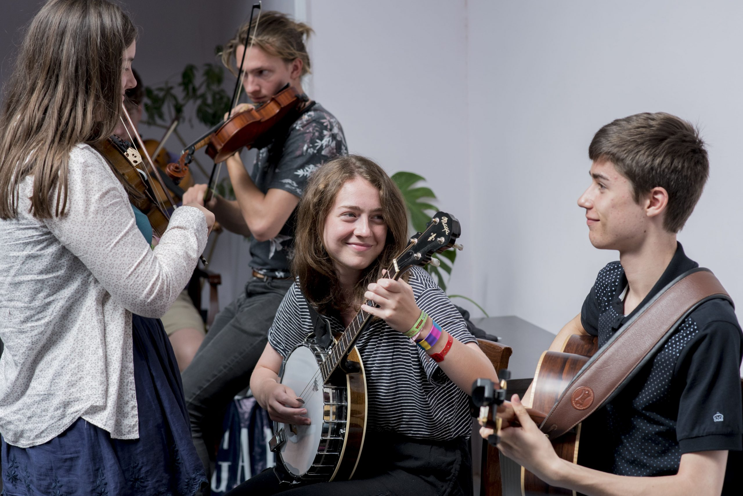 A girl with brown hair to her shoulders is playing a banjo. She is smiling and looking at a boy on the right of the picture. He has very short dark hair, and is also smiling. He appears to be playing a guitar, though it's mostly hidden. They are both seated.